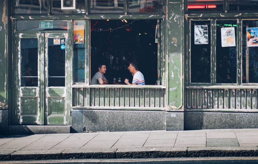 twee mannen zitten overdag in een bar